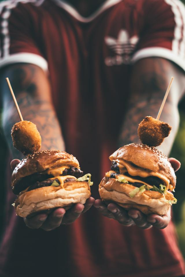 person-holding-two-hamburgers-1025804