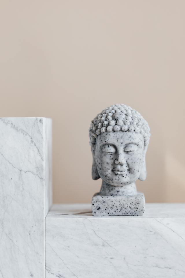 stone-bust-of-buddha-on-marble-shelf-4203072